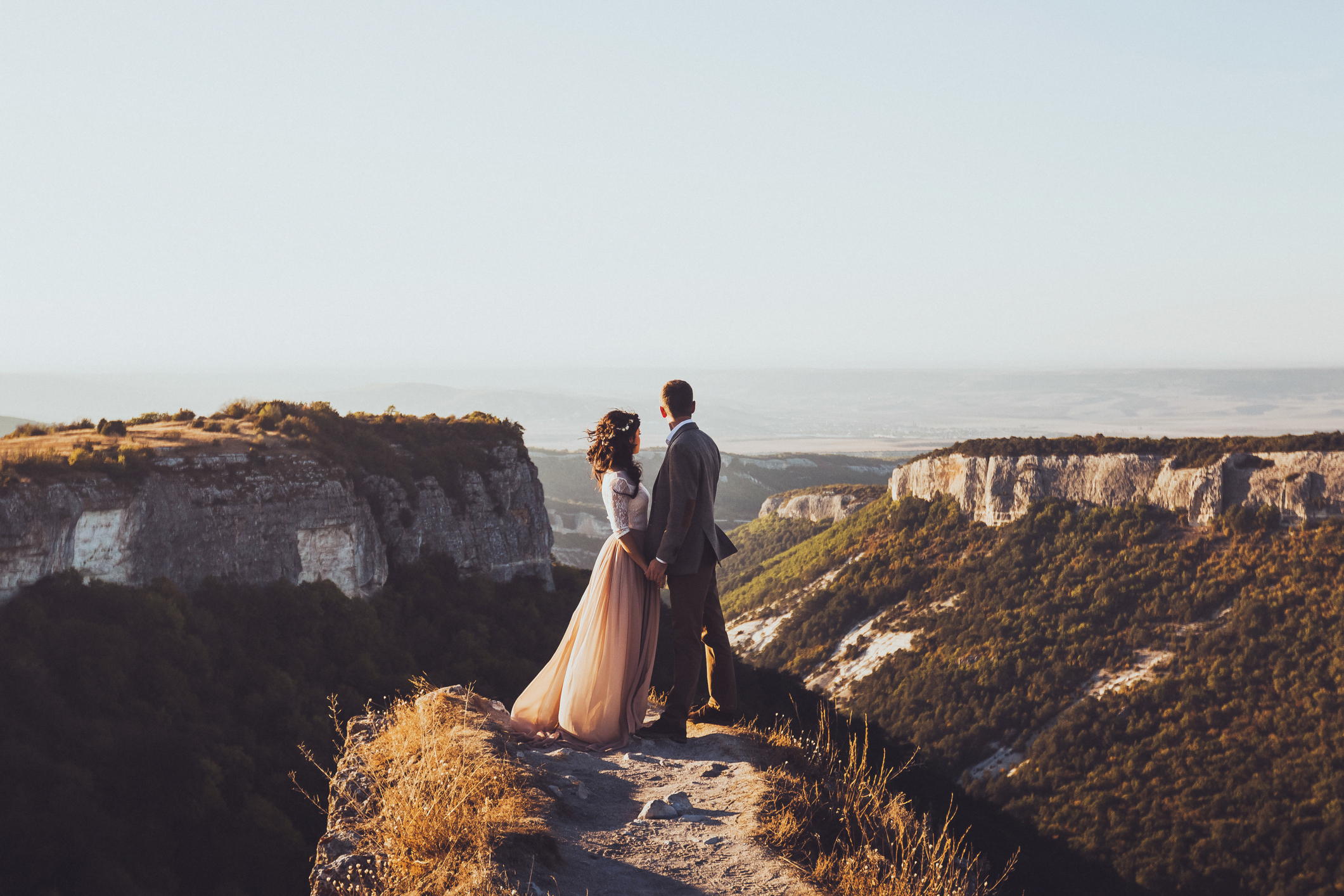 Bride and groom walking in mountains at sunset. Around the stunning scenery with views of the mountains and canyon Mangup